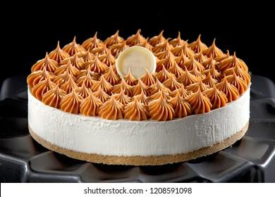 Cheesecake with caramel cream on black background