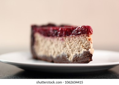 Cheesecake with chocolate crumb base topped with raspberry jelly