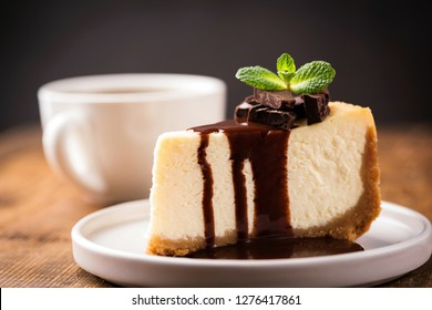 Cheesecake with chocolate sauce and cup of coffee. Slice of classical New York cheesecake poured with chocolate sauce and decorated with mint leaf