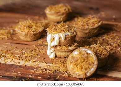 Cheesecake cookie cups baked in a muffin tin. Homemade cookies with cream cheese filling and kataifi dough on the top. Traditional Middle Eastern dessert on the wooden table. - Image