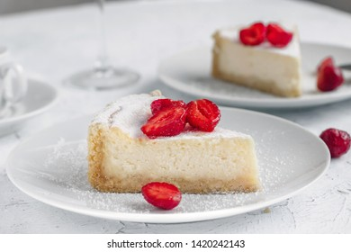 Cheesecake decorated with strawberries on a white plate
