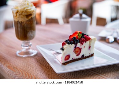 cheesecake with fresh fruit and iced coffee in the background
