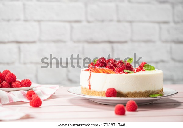 Cheesecake with fresh raspberries, plums and mint leaves.
