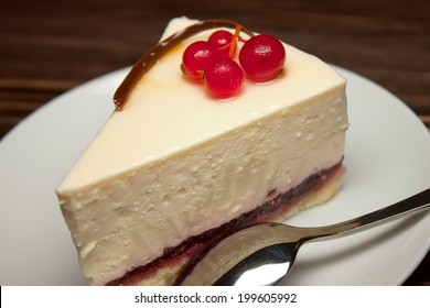 cheesecake with fresh red currants on a brown wooden background