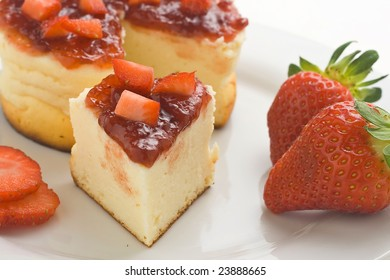 cheesecake with fresh strawberries and blackberry jam isolated over white