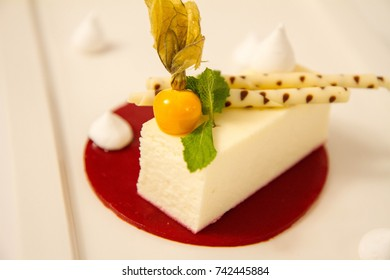 Cheesecake with fruit sauce decorated with physalis fruit, meringues and white chocolate