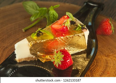 Cheesecake in gold leaf with strawberries