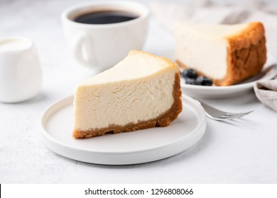 Cheesecake New York with cup of coffee on white table. Closeup view. Coffee break with slice of cake and black coffee