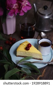 cheesecake on a plate and cup with cherries and a bouquet of peonies nearby
