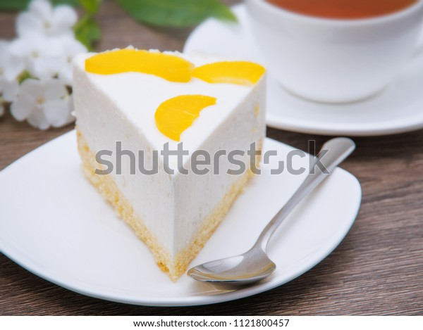cheesecake with peaches on white plate