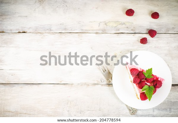 cheesecake with raspberries on a white wood background. toning. selective focus on leaves