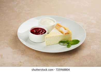 Cheesecake with raspberry sauce and sour cream. decorated with mint. on a white background