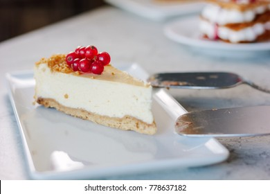 Cheesecake with red currant berries on white plate.