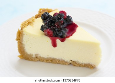Cheesecake slice. Berry topping. Close view. Copy space.Blue background.