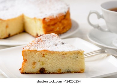 Cheesecake slice on white wooden background.