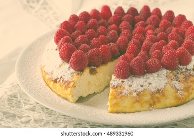 Cheesecake, souffle, cream mousse, pudding dessert with fresh raspberries and mint leaves on a white plate