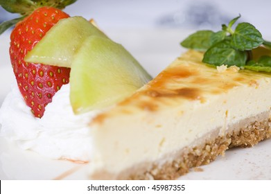 Cheesecake with strawberry and cream on a white plate