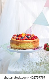 Cheesecake topped with fresh berries, fruits and white flowers