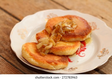 cheesecakes with sauce from pears on an old plate