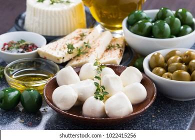 cheeses - mozzarella, feta cheese and pickles on table, horizontal