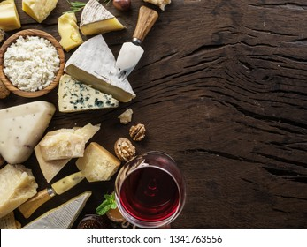 Cheeses with organic cheeses, fruits, nuts and wine on old wooden background. Top view. Tasty cheese starter.
