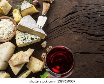Cheeses with organic cheeses, fruits, nuts and wine on wooden background. Top view. Tasty cheese starter.