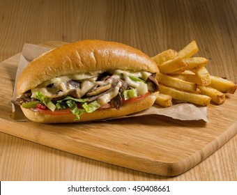 cheesesteak sandwich on cutting board with fries