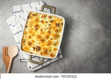 Cheesy cauliflower casserole on concrete background. Top view, space for text, toned.
