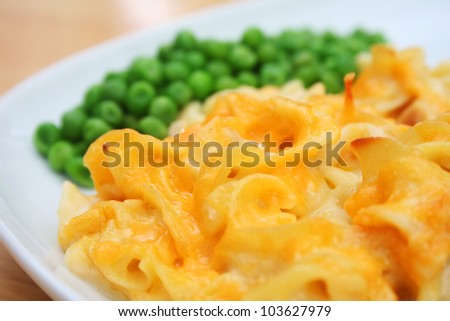 Cheesy Noodle Casserole and Peas on a White Dish