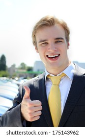 Cheesy Professional Business Man Car Salesman at Car Sales Lot Arms Crossed Looking At Camera Blonde Concept