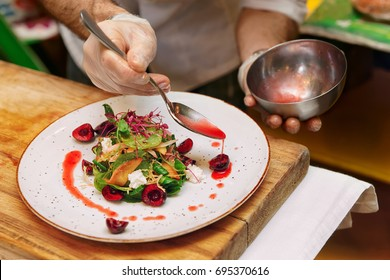 Chef is adding red sauce to vegetable and berry appetizer, toned image