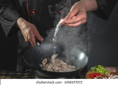 Chef adding salt by cooking chicken and vegetables in wok pan by cook hands on black background.