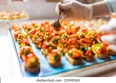 Chef adding special dressing on colored canapes
