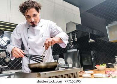chef adding thyme twig on frying pan