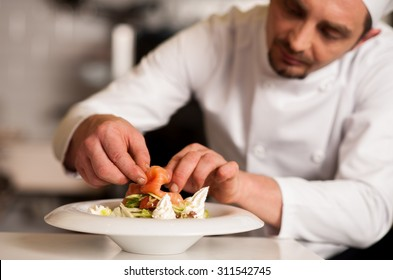 Chef adding topping for smoked salmon salad
