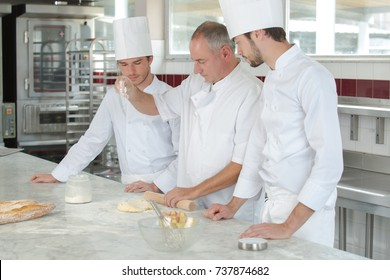 chef and apprentices working at kitchen
