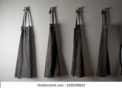 Chef Aprons Four in a Row Hanging in a Kitchen. Grey Kitchen Aprons Hanging on the wall.