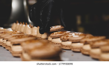 Chef is assembling caramel macarons. Close-up of hand in glove is puts a shells on french cookies.