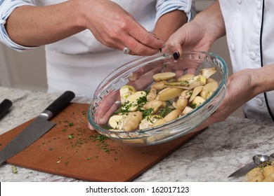 Chef and assistant preparing potatoes, adding ingredients