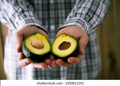 Chef with avocado. Man holding fresh avocado fruit