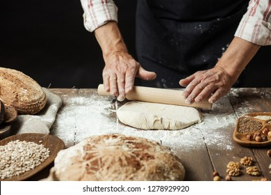Chef or baker, dressed in black apron, preparing a portion of fresh dough in rural bakery, kneading the pastry surrounded by rustic organic loaf of bread.