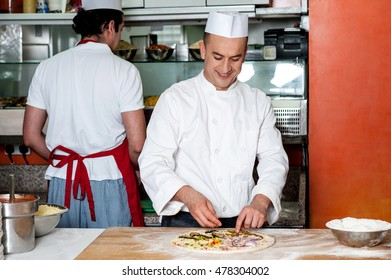 Chef baker in white uniform making pizza at kitchen