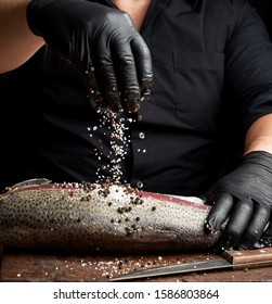 chef in a black shirt and black latex gloves prepares salmon fillet on a wooden cutting board, process of sprinkling with spices and salt, low key