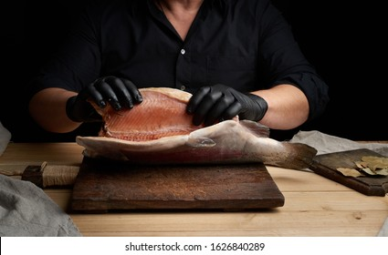 chef in a black shirt and black latex gloves holds a raw carcass of headless salmon fish over a brown wooden cutting board, process of cutting fish