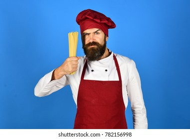 Chef with bunch of spaghetti. Cooking italian food concept. Cook with serious face in burgundy hat and apron holds dry pasta. Man or hipster with beard holds macaroni on blue background.
