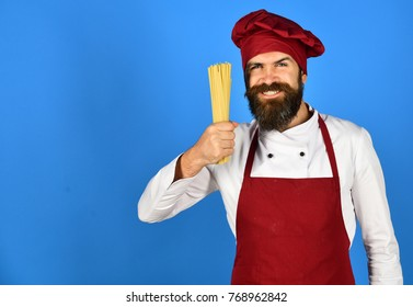 Chef with bunch of spaghetti. Man or hipster with beard holds macaroni on blue background, copy space. Italian restaurant concept. Cook with happy face in burgundy hat and apron holds dry pasta.