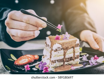 chef chocolate pastry dessert flower plate fine garnish icing making cake cooking food perfect dining adding building concept - stock image