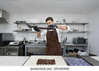 Küchenchef oder Schokoladenköchler fertigen Süßschokolade in einer professionellen Küche. Er dreht die Form um und gießt den Rest der Schokolade auf den Tisch.