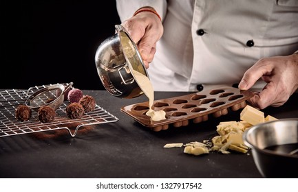 Chef or chocolatier pouring melted white chocolate into silicone molds from a saucepan in a close up on his hands
