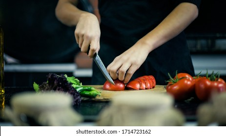 a chef chopping tomatoes with a knife